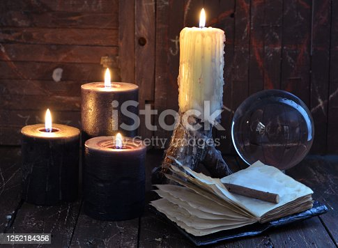 811119304 istock photo Creepy still life with burning candles, crystal ball and open diary on witch table. 1252184356
