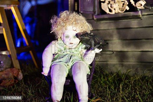 DIY Halloween doll holding pretend rat in creative yard of Halloween decorations