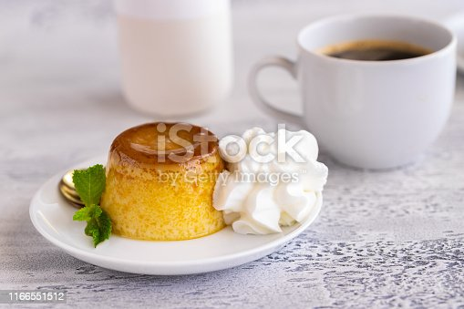 Creme caramel dessert or flan  decorated  with whipped cream and mint  and served with cup of coffee. Sweet moment background.