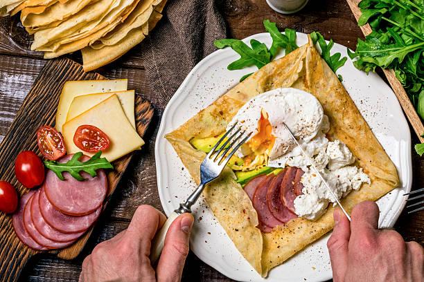 crêpe mit schinken, käse, avocado und ei - buchweizenpfannkuchen stock-fotos und bilder