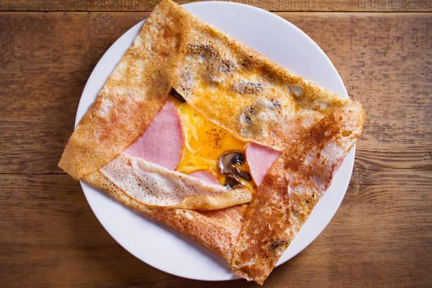 Crepes, panqueques finos con jamón, queso, huevo y champiñones. Panqueques con relleno en plato blanco - foto de stock