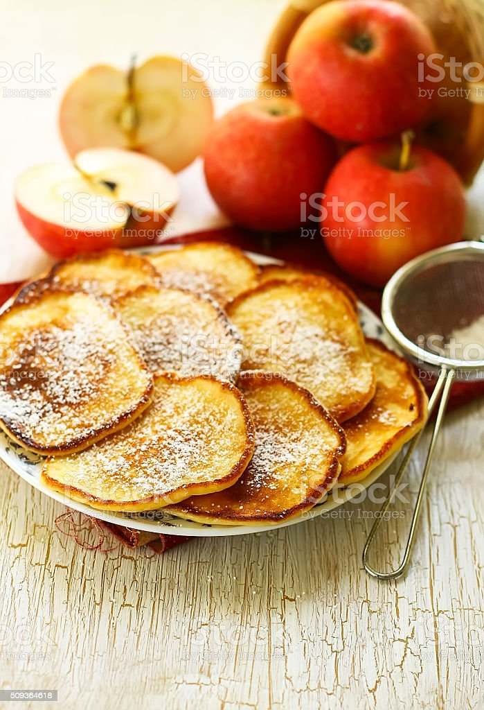 crepes with apples on a white wooden background stock photo