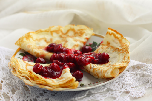 crepes with apples on a white wooden background