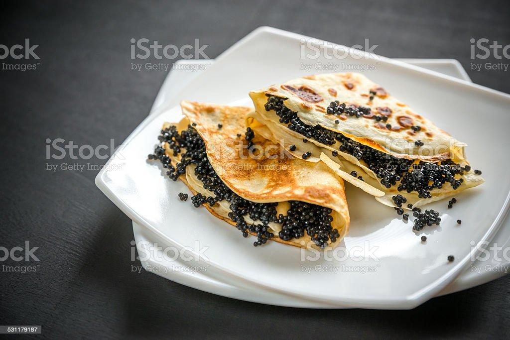 Crepes with black caviar stock photo