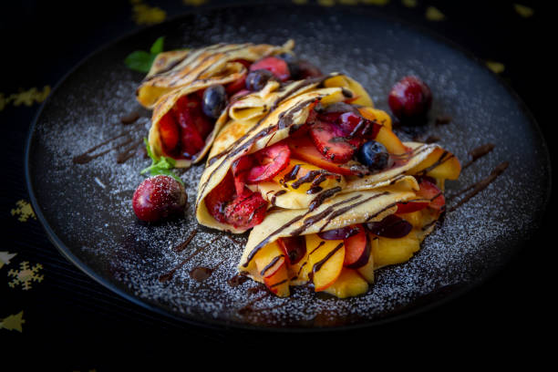 Crepes with Fresh Berries, Chocolate Sauce and Powdered sugar stock photo