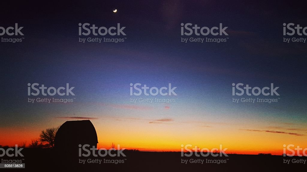 Crescent Moon Above an Iowa Farm at Sunset stock photo