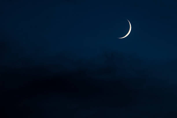 Crescent Moon in Cloudy Sky at Night stock photo