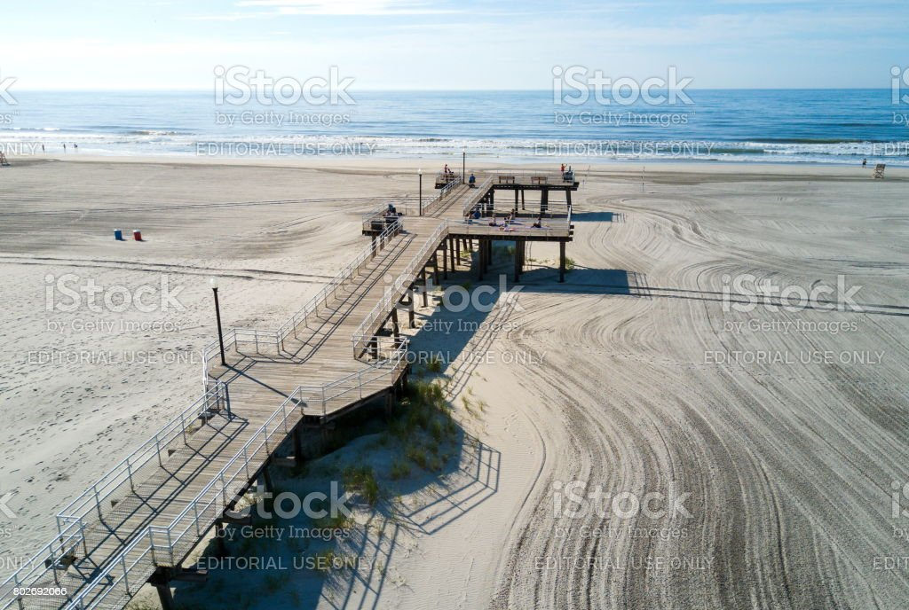 Crest beach and wooden dock from above with the ocean view and tourists relaxing stock photo