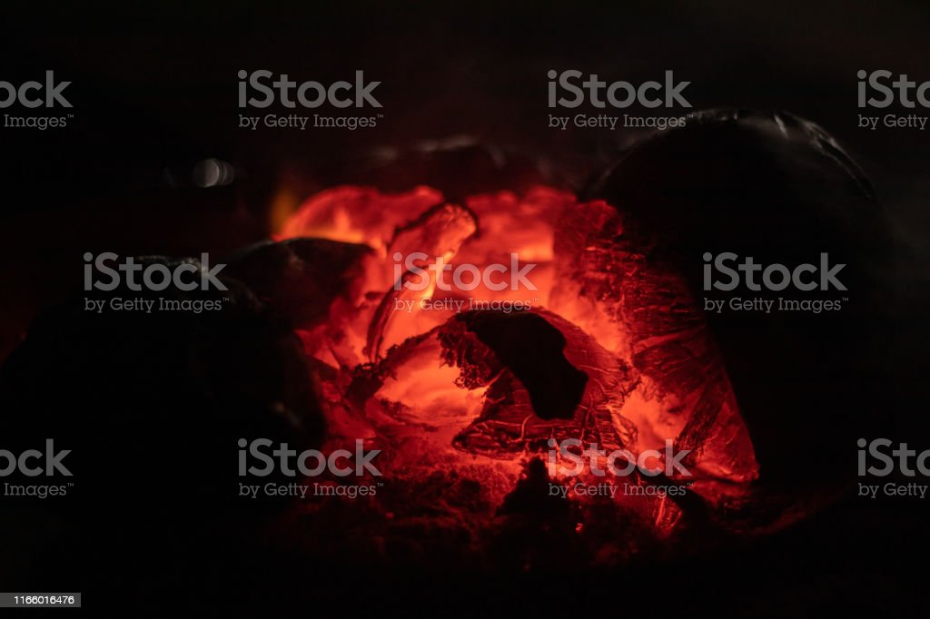 crest of flame on burning wood in fireplace India.