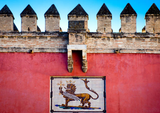 Crest on the exterior wall of Alcazar Castle in Seville The exterior wall of the Alcazar castle in Spain with a crest of a lion on the wall below the castellated top of the wall. alcazar palace stock pictures, royalty-free photos & images