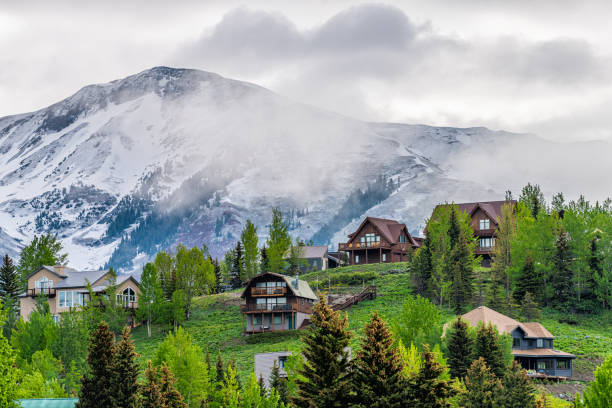Crested Butte, USA Colorado town village in summer with clouds and foggy mist morning and houses on hillside with green trees stock photo
