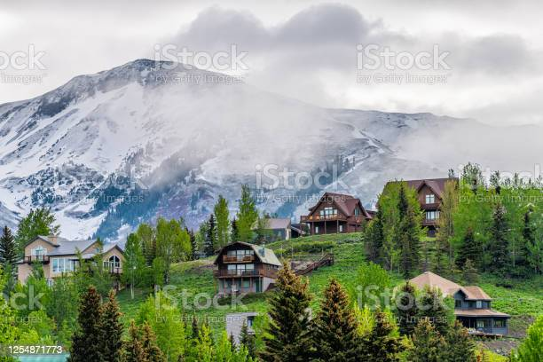 Photo of Crested Butte, USA Colorado town village in summer with clouds and foggy mist morning and houses on hillside with green trees