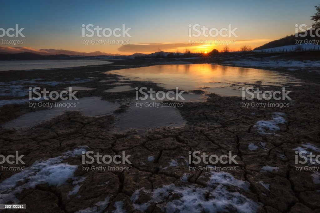 Crevices in the frozen mud in a cold morning stock photo