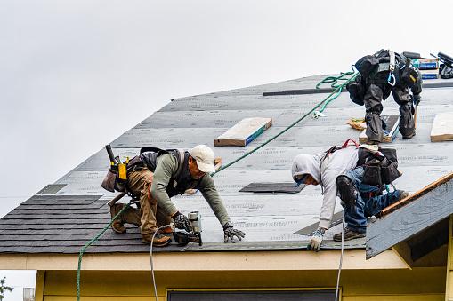 Everett WA. USA - 03-23-2021: Crew Installing New Shingles on Roof on a Rainy Day