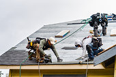 istock Crew Installing New Shingles on Roof on a Rainy Day 1310643662