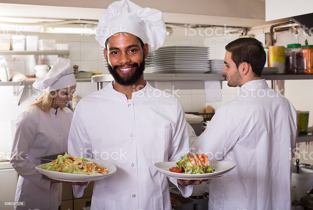 Crew of professional cooks working at restaurant royalty-free stock photo