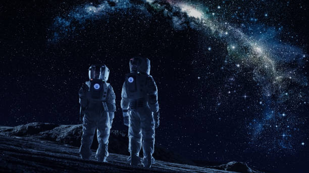 crew of two astronauts in space suits standing on the moon looking at the the milky way galaxy. high tech concept of moon colonization and space travel. - исследование космоса стоковые фото и изображения