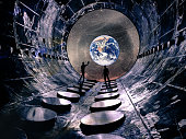 Crew of two astronauts standing in the tunnel looking at the the planet Earth and milky way galaxy. High tech concept of Moon colonization and space travel.  Elements of this image furnished by NASA.