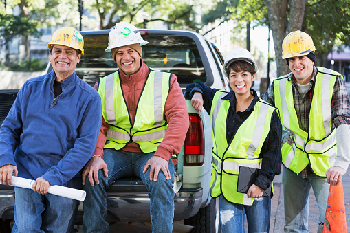A group of four diverse workers wearing hard hats and yellow safety vests with pickup truck on city street.  They are a crew of construction or utility workers, smiling at the camera.  One of the workers is a woman and two are Hispanic.