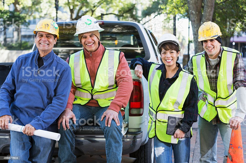 Crew of workers with hardhats and safety vest in city stock photo
