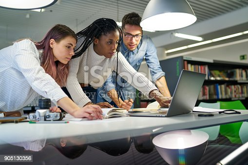 905130626 istock photo Crew of young marketing experts making productive work developing advertising strategy for websites watching promotional video and pointing on monitor, concentrated students browsing information 905130356