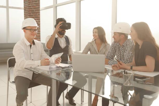 Crew junger professioneller Designer diskutiert Ideen zur Blaupause beim Besprechungstisch im modernen Studio – Foto