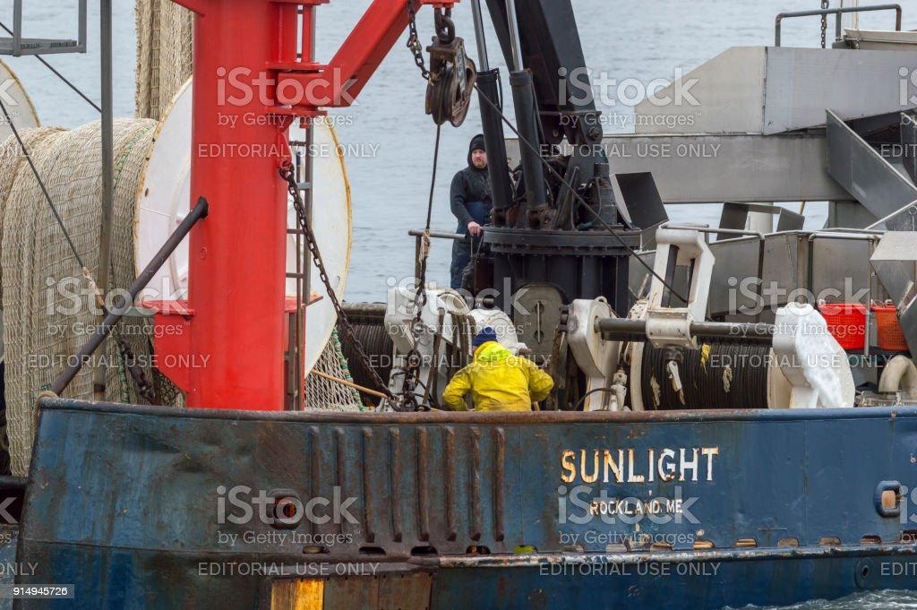 Crewmen securing gear aboard fishing trawler stock photo