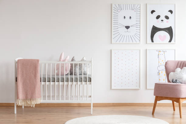 Crib in baby room White crib with pink blanket and decorative cushions standing in cute baby room with posters crib stock pictures, royalty-free photos & images