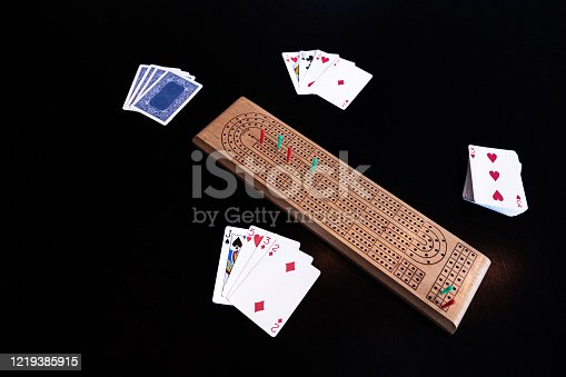 Cribbage board and cards set up on black table with pegs set up showing imminent victory.