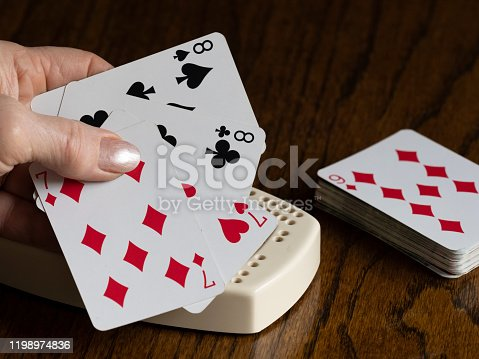 Playing cards in a senior woman's left hand. This is both the red and black playing card suits, close-up with the cribbage board slightly showing. Edited.