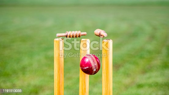 Close-up photo of a cricket ball hitting the stumps and knocking off the bails.