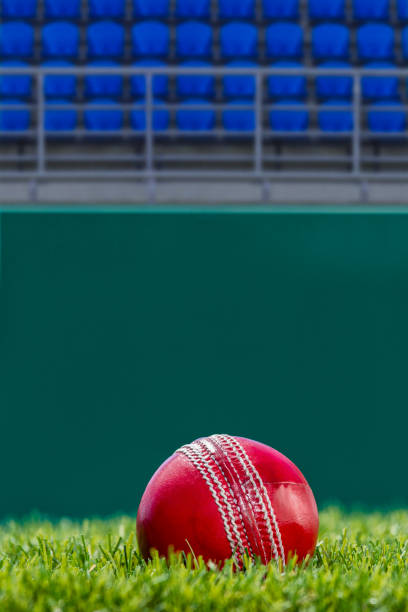 A Cricket ball sitting on the grass pitch with empty blue seats in the background