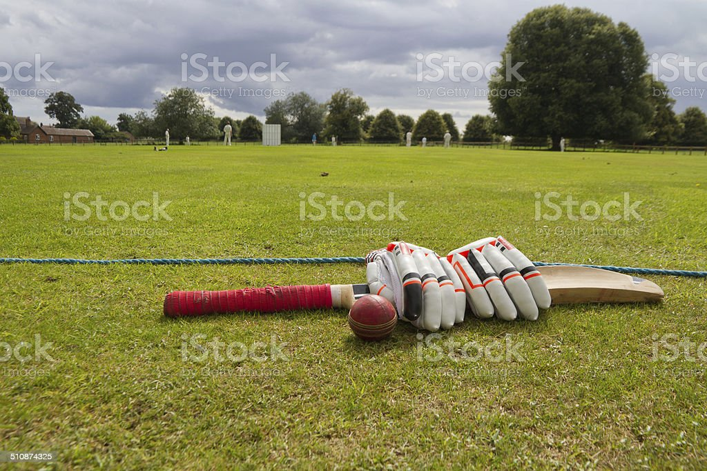 Cricket bat and gloves on English village green. stock photo