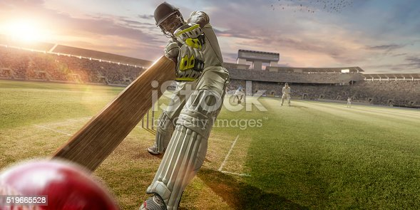 A close up image of a professional cricketer playing in batsman position wearing cricket whites and safety helmet, having just hit a ball during a cricket match in an outdoor stadium full of spectators. The action occurs under an evening sky at sunset. Stadium is fake, created from photographic and CG elements.