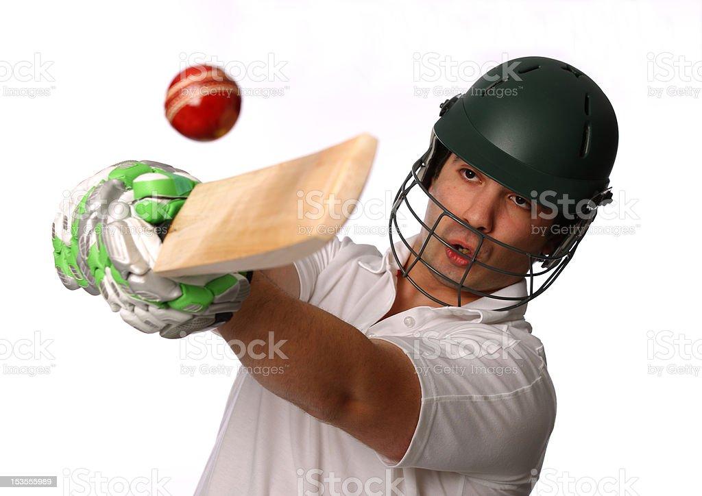Cricket batsman swinging at ball stock photo