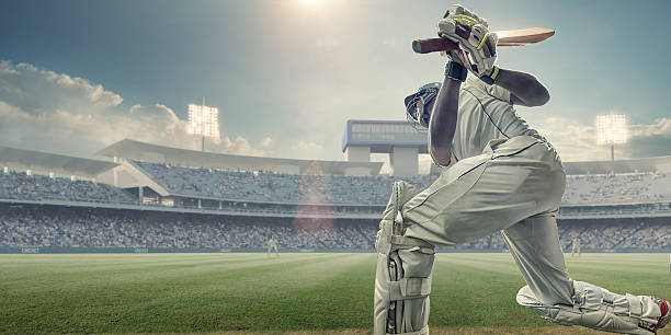 cricket batsman with bat up after hitting ball in game - cricket stock photos and pictures