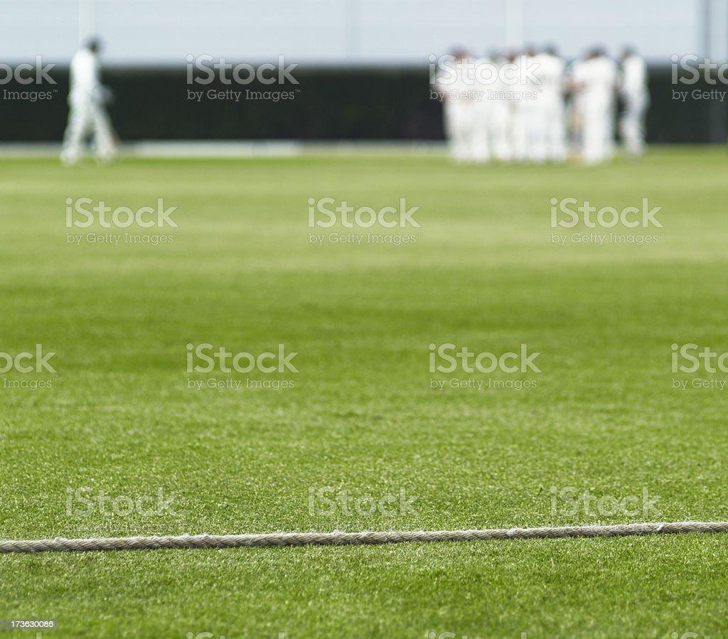 Cricket boundary rope and walking batsman royalty-free stock photo