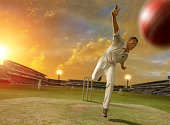 selective focus image of game of cricket action inside a stadium showing bowler bowling