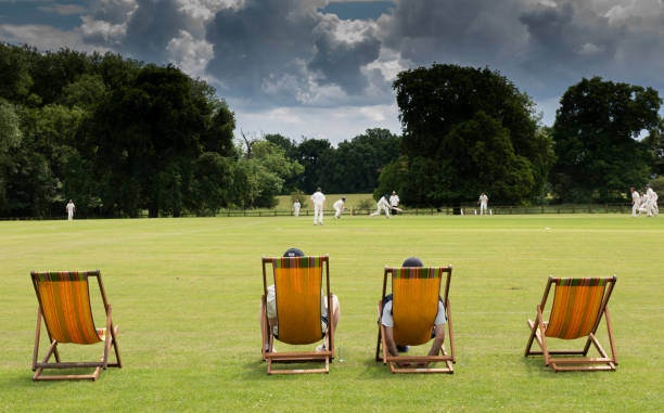 cricket in on an English village green watching a cricket match on a typical English cricket ground in summer sport of cricket stock pictures, royalty-free photos & images