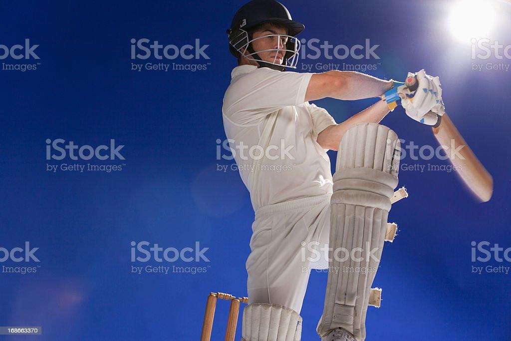Cricket player swinging bat stock photo