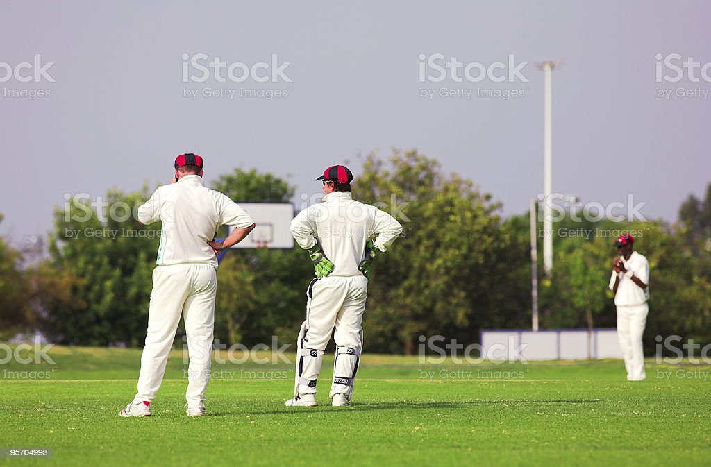 Cricket players standing around waiting on the field royalty-free stock photo