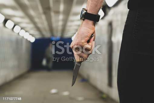 Crime and security concept - a thief with a knife is going to attack and rob another person in a tunnel.