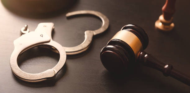 Crime and violence concept with handcuffs Handcuffs and wooden gavel. Crime and violence concept. criminal stock pictures, royalty-free photos & images