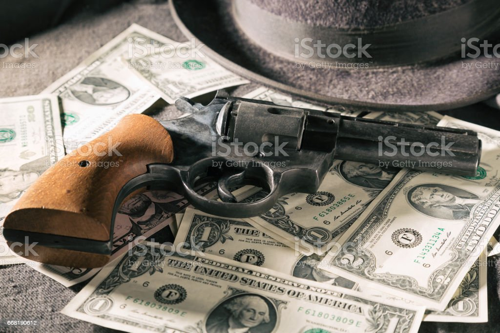 Crime concept. Black gun with dollar banknotes and hat. Toned image stock photo