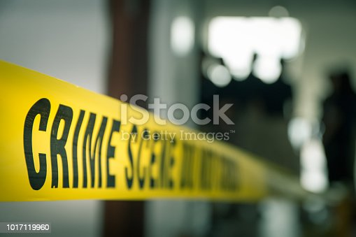 crime concept by police line tape with blurred forensic law enforcement background in cinematic tone and copy space