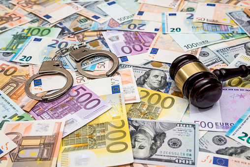 istock crime concept - handcuffs, gavel dollar and euro bills 924744604
