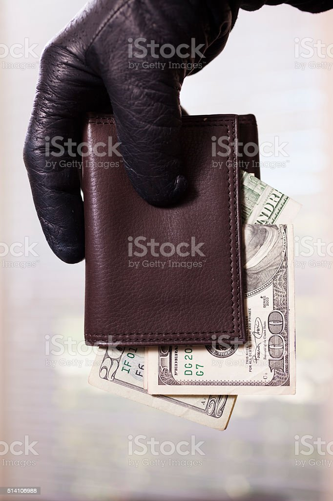 Close up of a theif wearing a black glove stealing a victim\'s wallet...