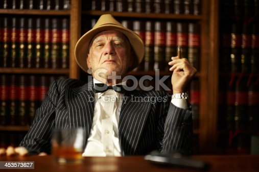 Aged mob boss smoking a cigar and looking serious from behind his desk