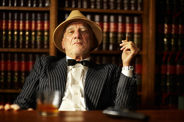 Crime is all about control Aged mob boss smoking a cigar and looking serious from behind his desk gangster stock pictures, royalty-free photos & images