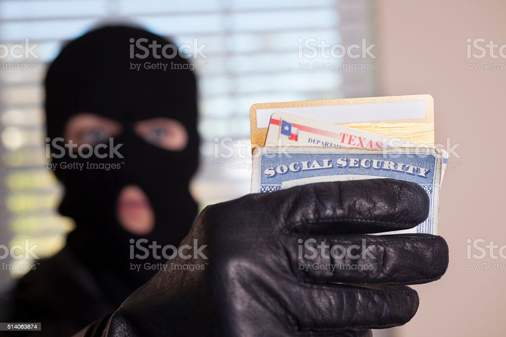 Crime: Masked theif steals identification cards. stock photo